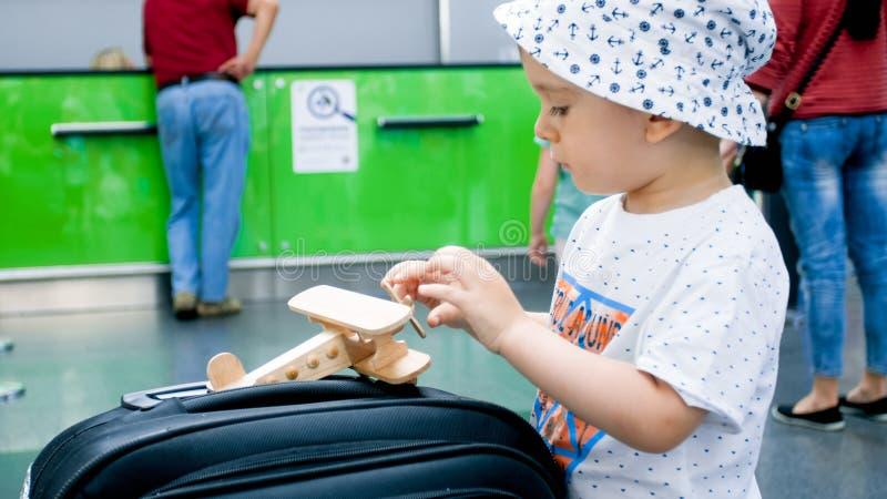 使用与在大手提箱的玩具飞机的小男孩的特写镜头图象在机场 免版税图库摄影