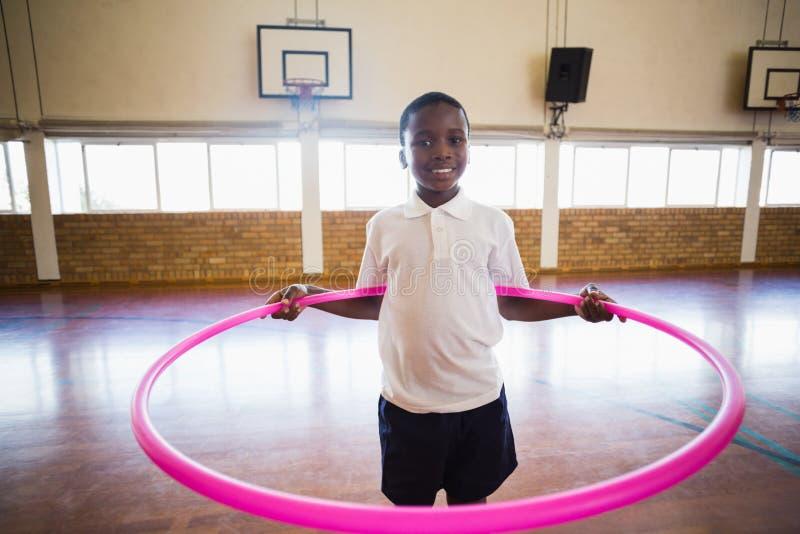 使用与在学校健身房的hula箍的男孩画象 免版税库存照片