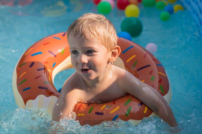 使用与在室外游泳场的五颜六色的可膨胀的圆环的愉快的儿童男孩在热的夏日 孩子学会游泳 儿童水 免版税库存照片