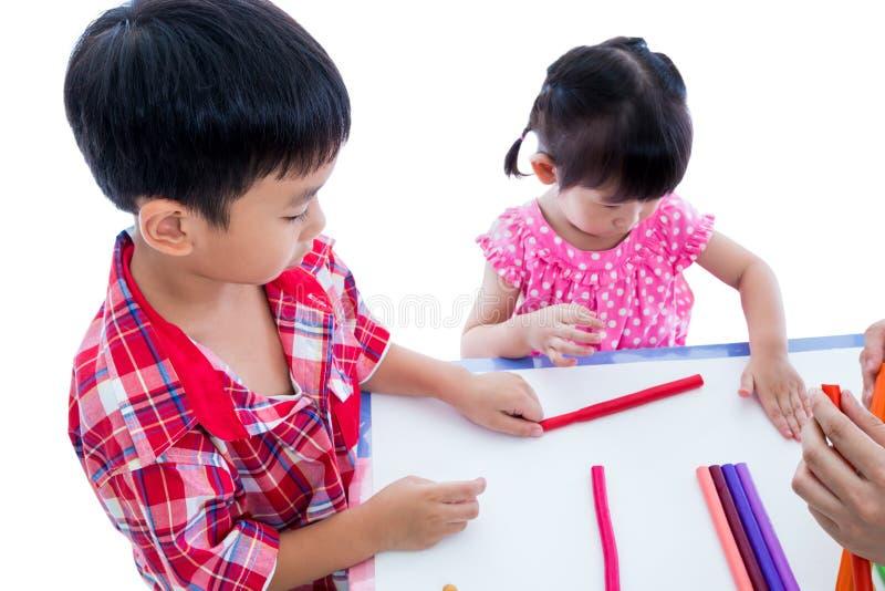 使用与在桌上的戏剧黏土的亚洲孩子 加强imagi 免版税库存照片