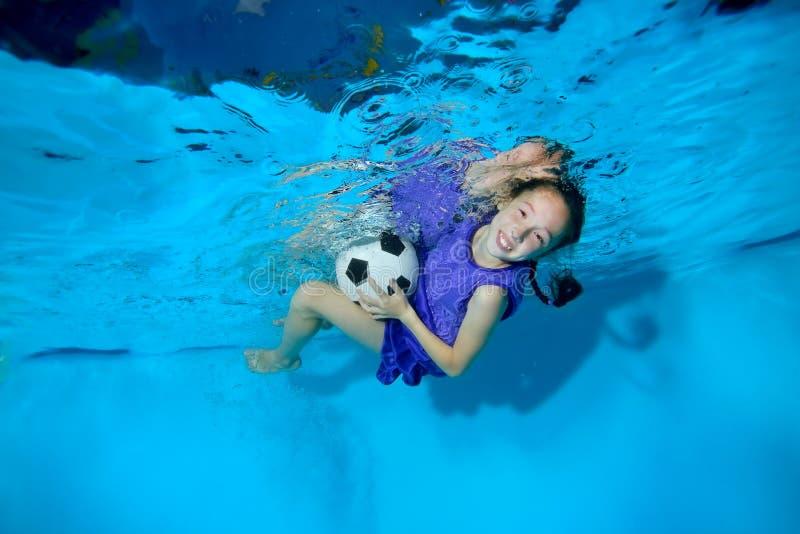 使用与在水池的足球水中的一个小女孩在蓝色背景 她看照相机并且微笑 画象 库存照片