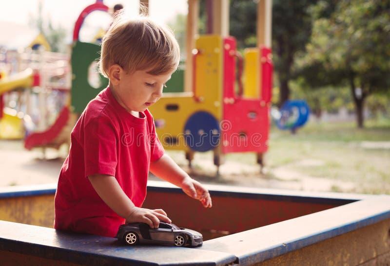 使用与在沙盒的玩具汽车的年轻男孩 免版税图库摄影