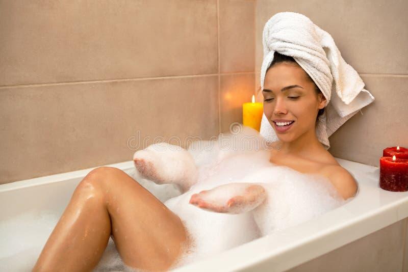 使用与在浴缸的泡沫的性感女孩 免版税库存图片