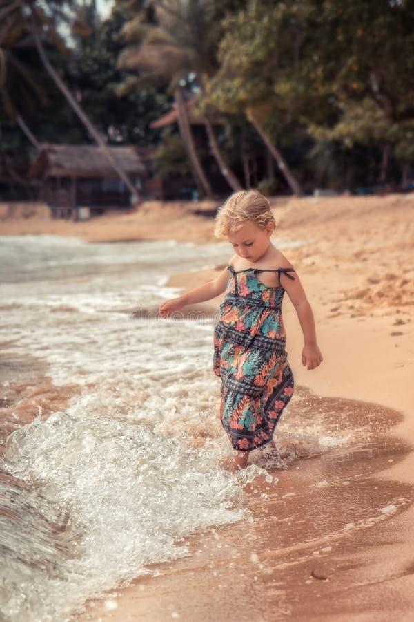 使用与在海滩热带海岛上的波浪的漂亮的孩子女孩在夏天休假概念无忧无虑的童年旅行lifestyl期间 免版税库存图片