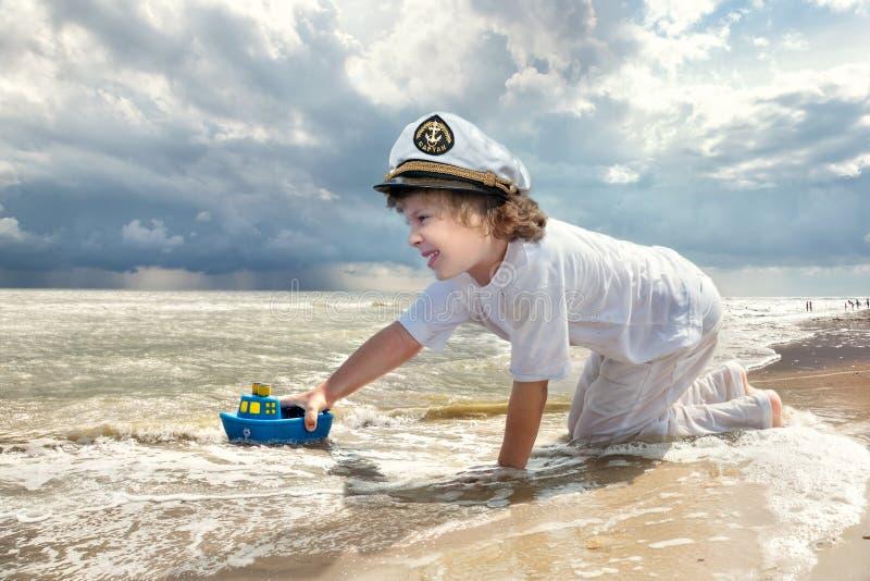 使用与在海滩的玩具船的小男孩温暖的夏日 库存图片