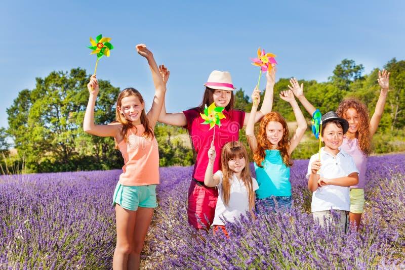 使用与在淡紫色领域的轮转焰火的逗人喜爱的孩子 免版税库存图片