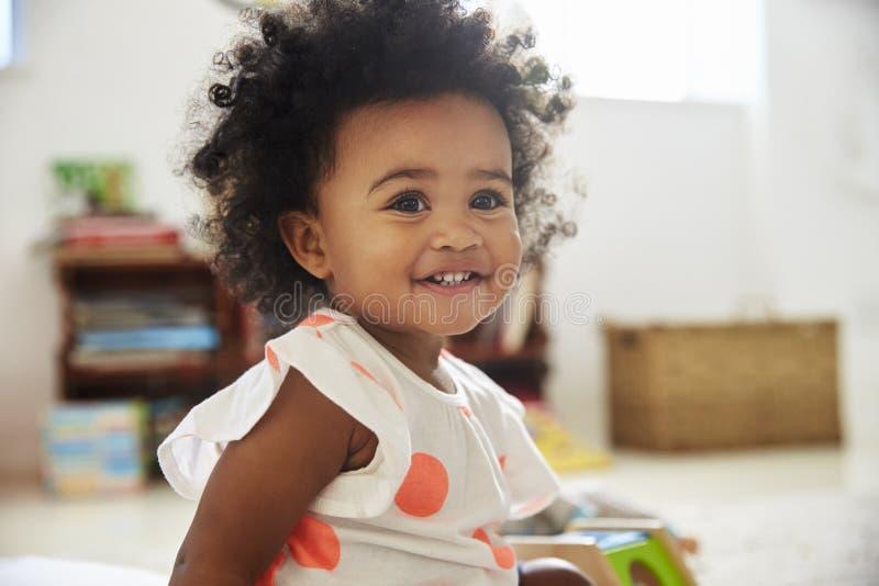 使用与在游戏室的玩具的愉快的女婴 免版税图库摄影