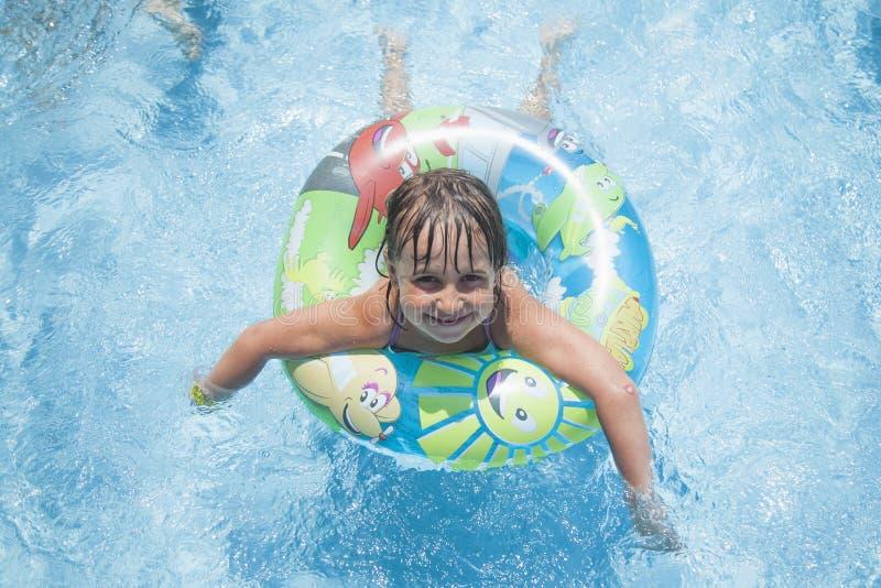 使用与在游泳场的五颜六色的圆环的愉快的逗人喜爱的小孩女孩滑稽的画象  孩子学会游泳 免版税库存图片