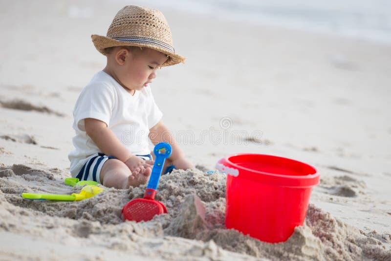 使用与在热带海滩的沙子的男婴 库存图片