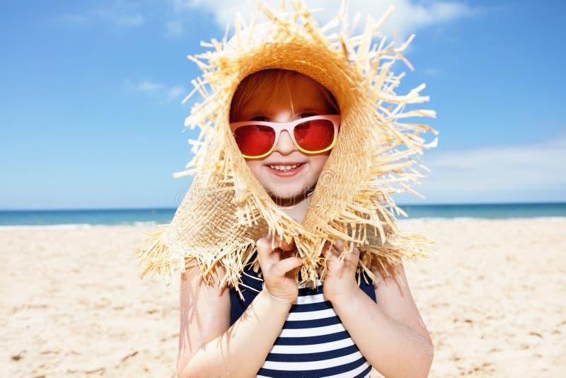 使用与在白色海滩的大草帽的泳装的女孩 免版税库存图片