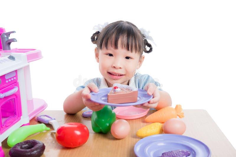 使用与在白色背景的厨房玩具的女孩 免版税库存照片