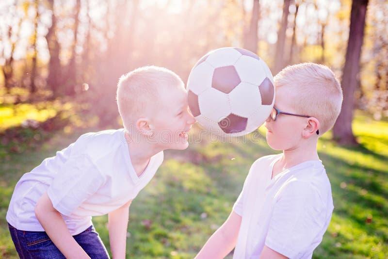 使用与在绿草的球的男孩兄弟在公园 图库摄影