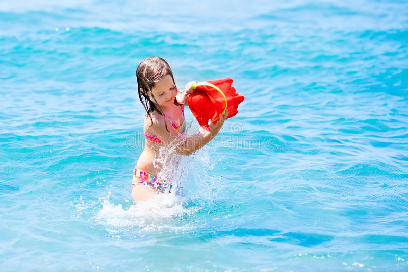 使用与在美丽的海滩的玩具桶的小女孩 库存照片