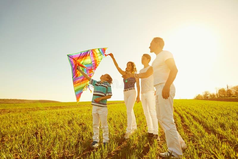 使用与在自然的一只风筝的愉快的家庭在春天,夏天 免版税图库摄影