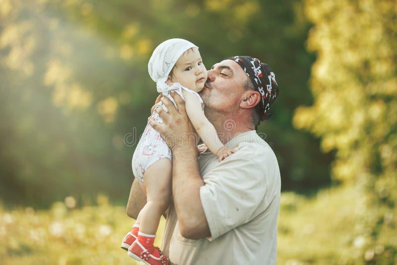 使用与在自然背景的可爱的女婴的年轻祖父 祖父母和孙悠闲时间概念 免版税库存照片