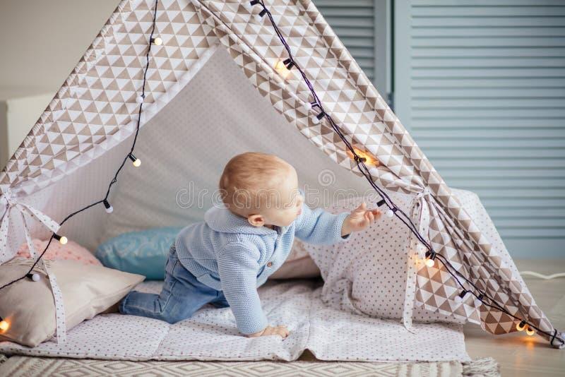 使用与在舒适蓝色游戏室的孩子帐篷的可爱的婴儿男孩 免版税库存照片