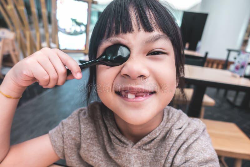使用与在饭桌上的匙子的亚裔女孩 库存照片