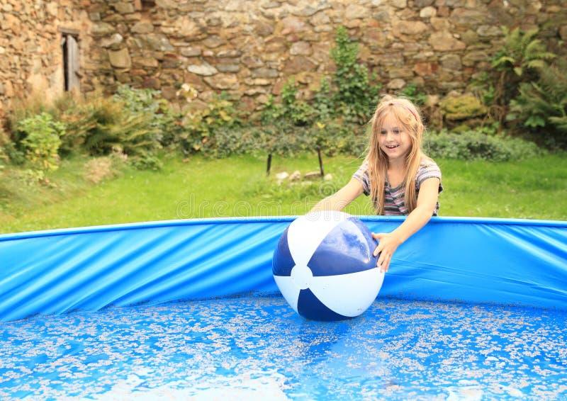 使用与在水池的球的小女孩 库存图片