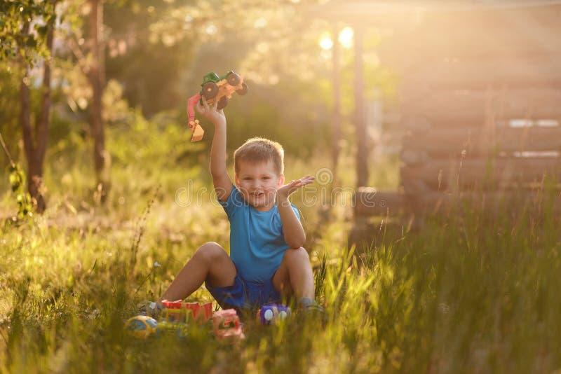 使用与塑料玩具的一件蓝色T恤杉和短裤的快乐的情感五岁的男孩在夏天坐草  库存照片
