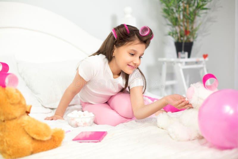 使用与填充动物玩偶的逗人喜爱的女孩在床上 免版税图库摄影