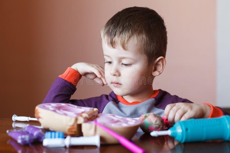 使用与多色彩的彩色塑泥的逗人喜爱的小男孩 使用与玩具牙齿工具的男孩 ?? 正面,消极 免版税库存照片