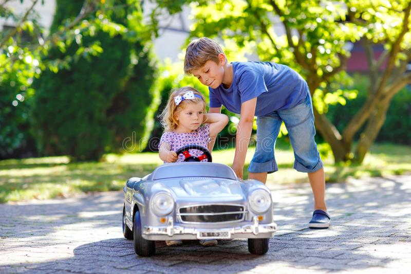 使用与大老玩具汽车的两个愉快的孩子在夏天庭院里,户外 驾驶有女孩的男孩汽车,逗人喜爱 免版税库存图片