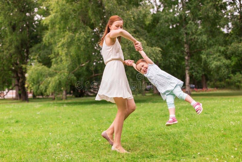 使用与女婴的愉快的母亲在夏天公园 库存照片