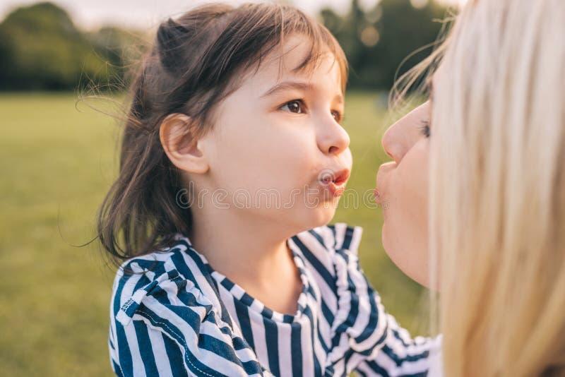 使用与她俏丽的母亲的愉快的逗人喜爱的女孩画象在公园 爱的母亲和女儿一起花费时间  免版税库存图片