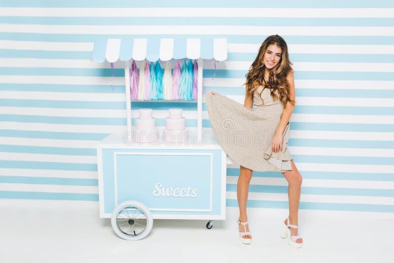 使用与她在柜台旁边的时髦的礼服身分的可爱的快乐的女孩与甜点 迷人的亭亭玉立的年轻女人  免版税库存照片