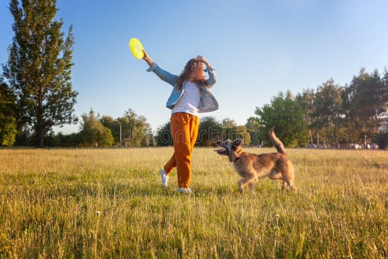 使用与她的与一个飞碟的狗的年轻美丽的卷曲女孩在夏天公园 免版税库存图片