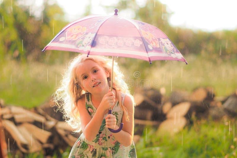 使用与她的伞的女孩在公园在一下雨天 免版税库存照片