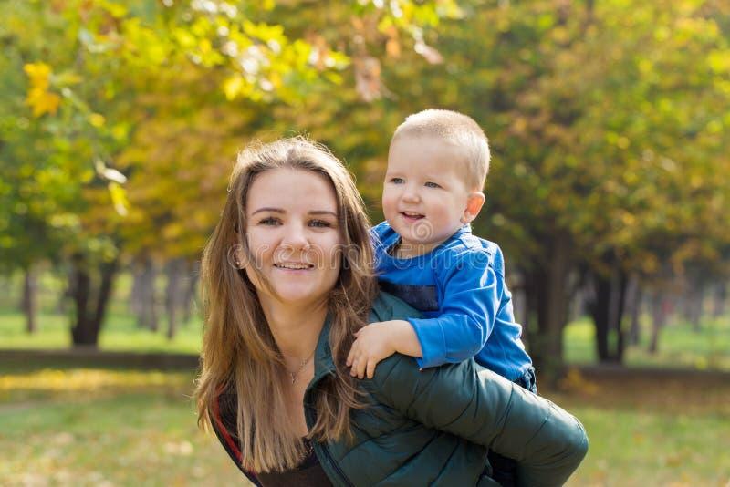 使用与她的儿子的愉快的母亲在公园 免版税图库摄影