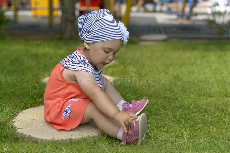使用与她的凉鞋的女孩坐绿草 免版税库存图片