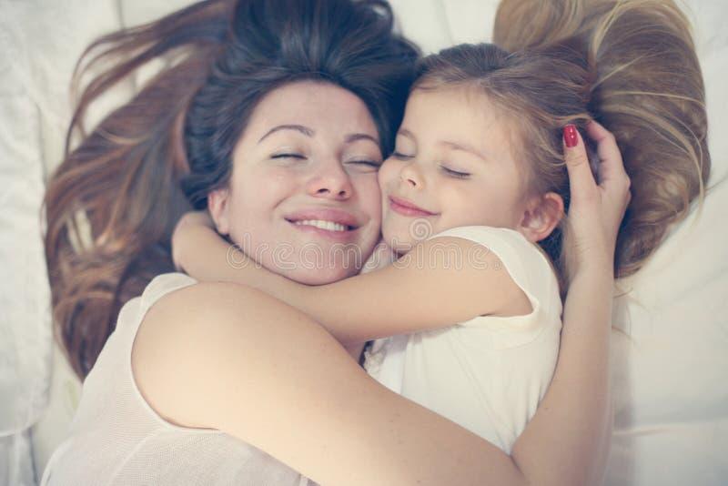 使用与她的在床上的小女儿的年轻母亲 免版税库存照片