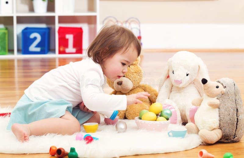 使用与她的填充动物玩偶的小孩女孩 免版税库存照片