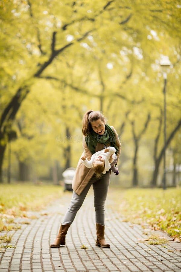 使用与她的女儿的年轻母亲在秋天公园 图库摄影