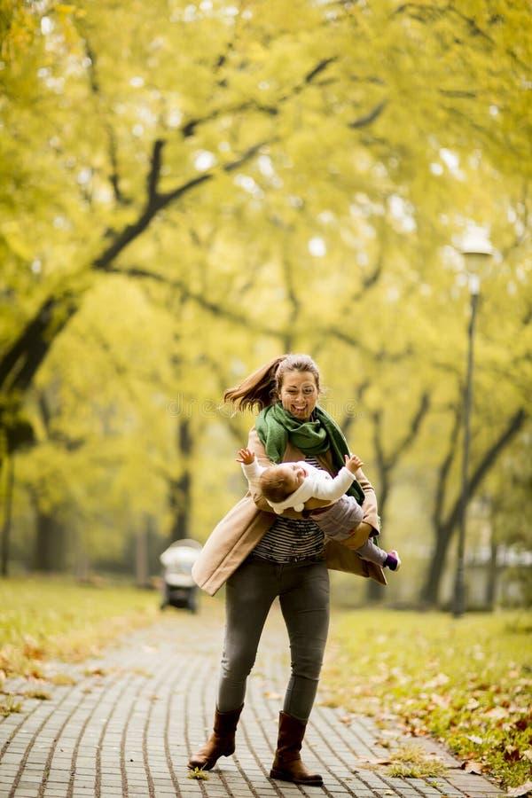 使用与她的女儿的年轻母亲在秋天公园 库存图片