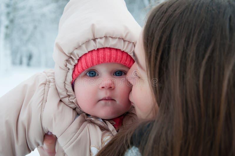 使用与她的妈妈的儿童女孩在冬天森林里 免版税图库摄影