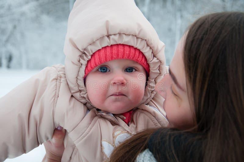 使用与她的妈妈的儿童女孩在冬天森林里 免版税库存图片