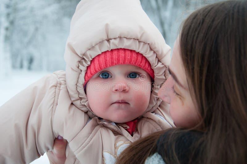 使用与她的妈妈的儿童女孩在冬天森林里 库存照片