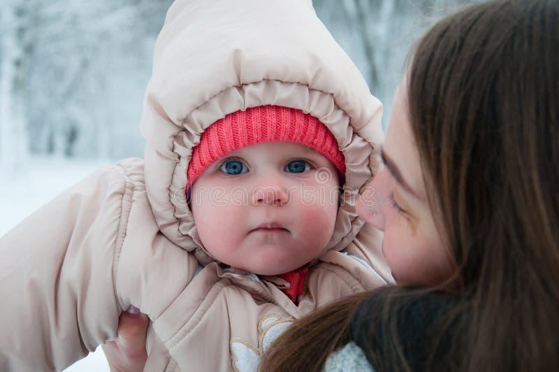 使用与她的妈妈的儿童女孩在冬天森林里 图库摄影