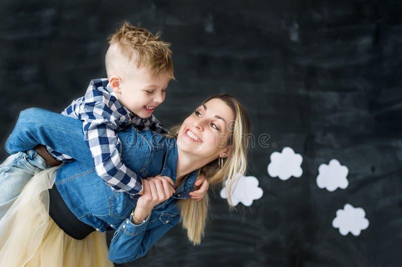 使用与她的孩子的爱恋的年轻母亲画象  拿着在她的头上的嬉戏的妇女小逗人喜爱的儿子 免版税库存图片