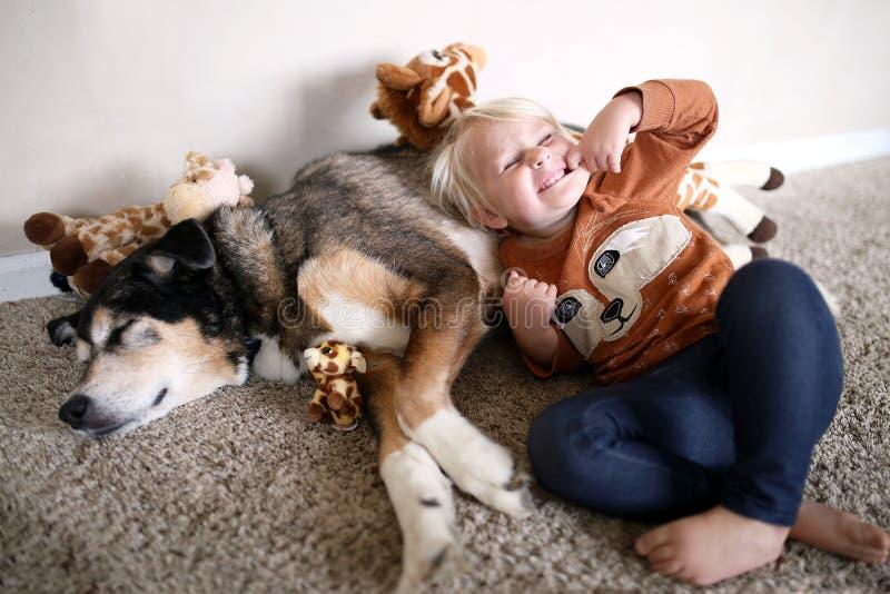 使用与她的宠物德国牧羊犬狗和长颈鹿的幼儿 免版税库存照片