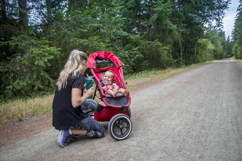 使用与她的小男孩的妇女,当一起跑步在足迹时 库存图片
