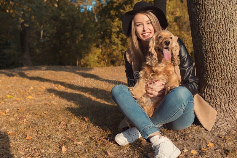 使用与她的狗的黑帽会议的美丽的逗人喜爱的愉快的女孩在一个公园在秋天另一个晴天 免版税库存照片