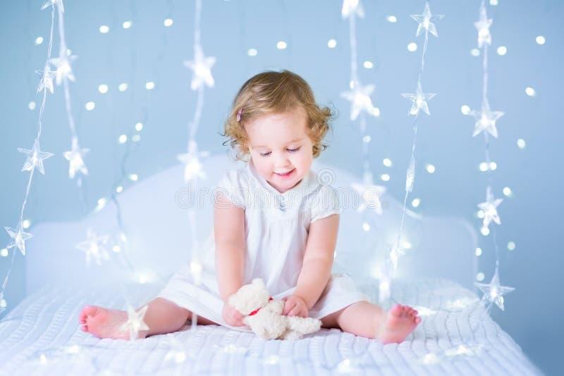 使用与她的玩具熊的甜小孩女孩在一间白色卧室之间 库存照片