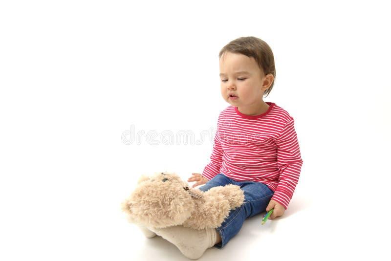 使用与她的玩具熊的甜小孩女孩把他放在脚上睡觉 图库摄影