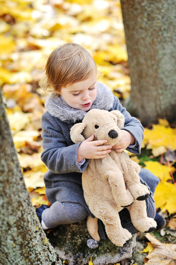 使用与她的玩具的小女孩在公园 免版税库存图片