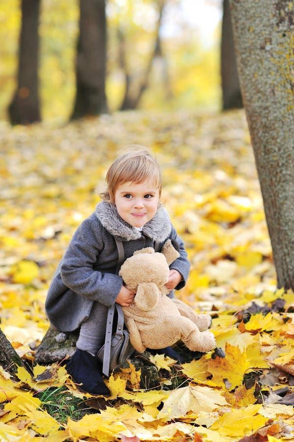 使用与她的玩具的逗人喜爱的小女孩在公园 库存图片