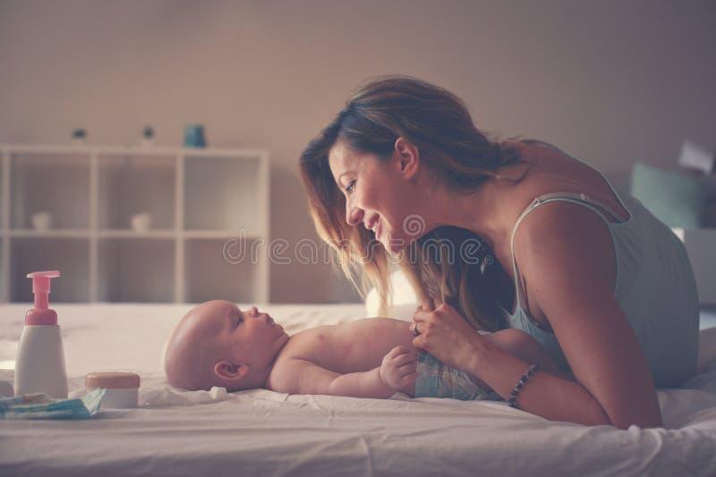 使用与她的男婴的年轻母亲在床上 享受i的母亲 图库摄影